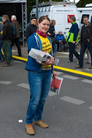 distributor: BERLIN - MAY 01, 2015:  International Labour Day. Distributor of free newspapers. Editorial