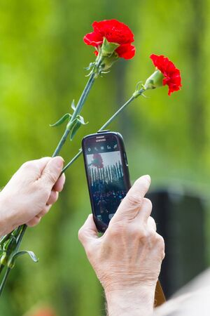memorable: BERLIN - MAY 08, 2015: Victory in Europe Day. Treptower Park. Red carnations and mobile phone. Member of the memorable events photographs at arms length.