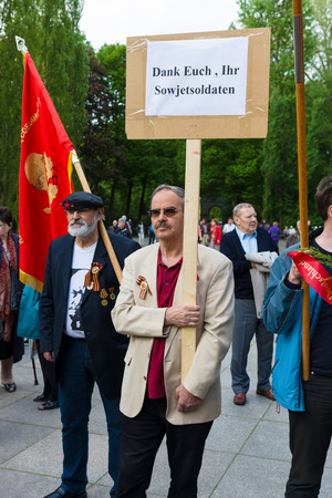 activists: BERLIN - MAY 08, 2015: Victory in Europe Day. Treptower Park. Communist activists at the memorable event. Text in German: Thank you, Soviet soldiers. Editorial