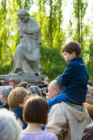 柏林 -  2015年5月08日:胜利在欧洲天。Treptower Park。纪念仪式的反法西斯仪式附近祖国雕塑。一个孩子坐在父亲的肩膀上。