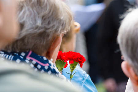 participants: BERLIN - MAY 08, 2015: Victory in Europe Day. Treptower Park. Participants of commemorative events with bouquets of carnations.
