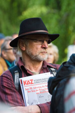 participants: BERLIN - MAY 08, 2015: Victory in Europe Day. Treptower Park. Distributor Communist Workers newspaper participants listening to a commemorative ceremony. Editorial