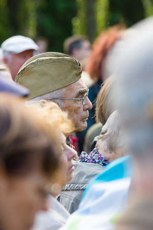 forage: BERLIN - MAY 08, 2015: Victory in Europe Day. Treptower Park. An elderly man in a soldiers forage cap listens participants commemorative ceremony.