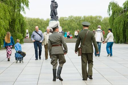 treptow: BERLIN - MAY 08, 2015: Victory in Europe Day. Two military officers in the form of the Soviet Union and the German Democratic Republic going on the background of the sculpture of a soldier in Treptow Park.
