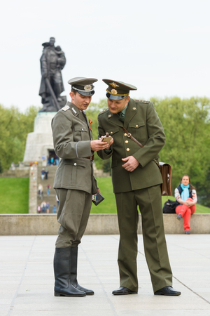 treptow: BERLIN - MAY 08, 2015: Victory in Europe Day. Two soldiers in the uniform of an officer of the USSR and the GDR posing against the backdrop a sculpture of a soldier in Treptow Park.
