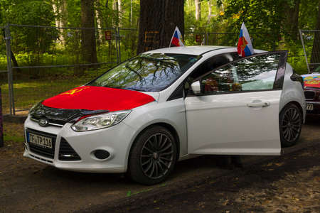 treptow: BERLIN - MAY 09, 2015: Victory Day. Car near the main entrance in Treptow Park decorated with the flags of the USSR and Russia.