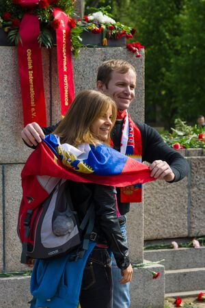 soviet flag: BERLIN - MAY 09, 2015: Victory Day in Treptower Park. Enamoured with the Russian flag and symbols are photographed against the backdrop of a memorial to Soviet soldiers.