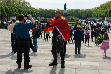 soviet flag: BERLIN - MAY 09, 2015: Victory Day in Treptower Park. The man with the flag of the Soviet Union is photographed against the backdrop of Soviet War Memorial.
