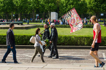 nazi flag: BERLIN - MAY 09, 2015: Victory Day in Treptower Park. Visitors to the memorial come with patriotic flags.