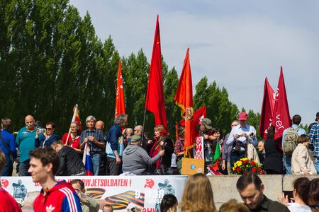 slogans: BERLIN - MAY 09, 2015: Victory Day in Treptower Park. Visitors to the memorial with Soviet flags and patriotic slogans.