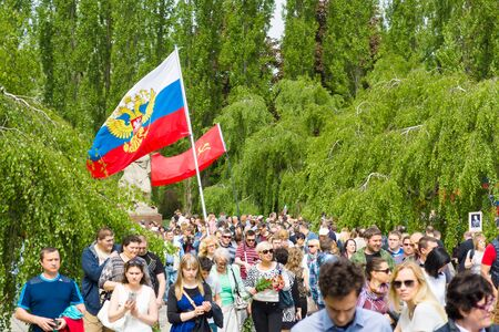slogans: BERLIN - MAY 09, 2015: Victory Day in Treptower Park. Visitors to the memorial with the flags of the USSR, Russia and patriotic slogans.