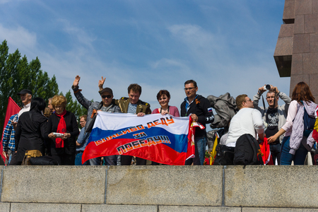 slogans: BERLIN - MAY 09, 2015: Victory Day in Treptower Park. Visitors to the memorial with Soviet flags and patriotic slogans. The inscription in Russian: Thanks to his grandfather for the victory! Editorial
