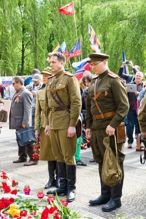 homage: BERLIN - MAY 09, 2015: Victory Day in Treptower Park. Soldiers in uniform during the war pay homage at the monument Motherland.