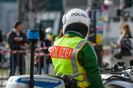 BERLIN - APRIL 03, 2016: The annual Berlin Half Marathon. Before the start of the race. A police officer on a motorcycle escort.