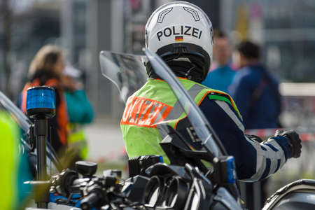 motorcycle officer: BERLIN - APRIL 03, 2016: The annual Berlin Half Marathon. Before the start of the race. A police officer on a motorcycle escort.
