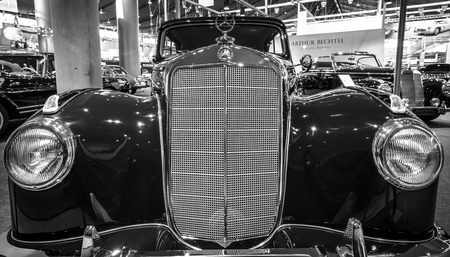 classics: STUTTGART, GERMANY- MARCH 17, 2016: Fragment of a full-size luxury car Mercedes-Benz 220 Cabriolet B (W187), 1953. Black and white.  Europes greatest classic car exhibition RETRO CLASSICS Editorial