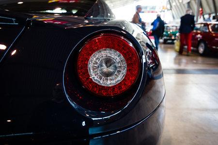 f1: STUTTGART, GERMANY - MARCH 18, 2016: The rear brake lights of sports car Ferrari 599 GTB Fiorano F1, 2008. Europes greatest classic car exhibition RETRO CLASSICS