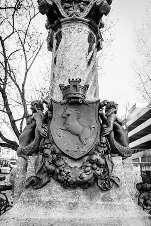 heinrich: STUTTGART, GERMANY - MARCH 18, 2016: The coat of arms of the state of Baden-Wuerttemberg on water source Nachtwaechterbrunnen (The fountain Night watchman) by Heinrich Halmhuber, 1900. Black and white.