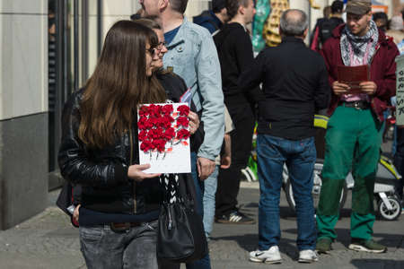 lapel: BERLIN - MAY 01, 2016: Woman with flowers (lapel badge). Members of trade unions, workers and employees at the demonstration on the occasion of Labour day.