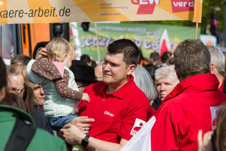 arms trade: BERLIN - MAY 01, 2016: A man with a child in her arms. Members of trade unions, workers and employees at the demonstration on the occasion of Labour day. Editorial
