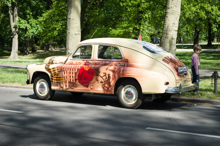 postwar: BERLIN - MAY 09, 2016: Victory Day in Treptower Park. The Soviet post-war car GAZ-M20 Pobeda (Victory) in patriotic Soviet painting on the military theme (airbrush).