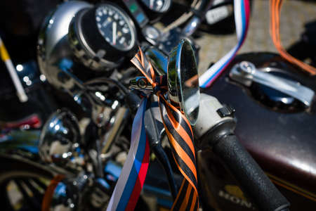 st german: BERLIN - MAY 09, 2016: Victory Day in Treptower Park. Motorcycles of Russian motorcycle club Night Wolves. Ribbons with colors of the Russian flag and St George on the motorcycle handlebar.