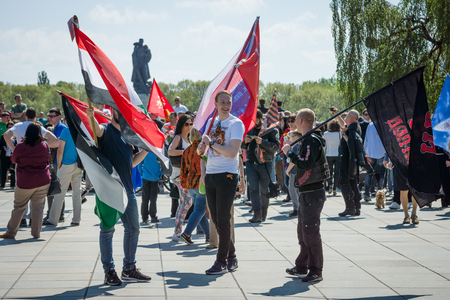 the liberator: BERLIN - MAY 09, 2016: Victory Day in Treptower Park. Guests with state flags of the Russian Federation, the Syrian Arab Republic and the flag of the motorcycle club Night Wolves on the background of the monument Liberator Soldier.