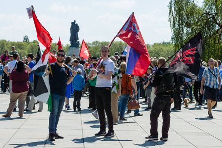 liberator: BERLIN - MAY 09, 2016: Victory Day in Treptower Park. Guests with state flags of the Russian Federation, the Syrian Arab Republic and the flag of the motorcycle club Night Wolves on the background of the monument Liberator Soldier.