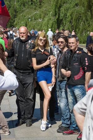representatives: BERLIN - MAY 09, 2016: Victory Day in Treptower Park. Guests of war memorial photographed with representatives of motorcycle club Night Wolves.