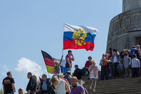 the liberator: BERLIN - MAY 09, 2016: Victory Day in Treptower Park. Guests and visitors at the foot of the monument to the Liberator Soldier with Russian and German flags. Editorial