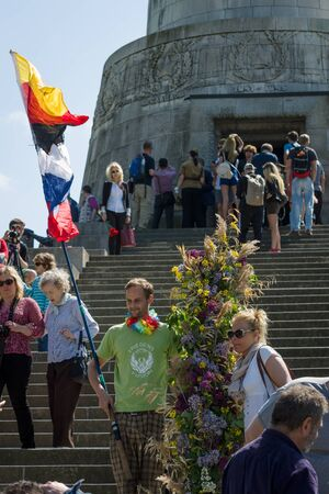 liberator: BERLIN - MAY 09, 2016: Victory Day in Treptower Park. Guests and visitors at the foot of the monument to the Liberator Soldier with Russian and German flags. Editorial