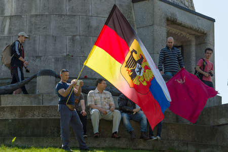 the liberator: BERLIN - MAY 09, 2016: Victory Day in Treptower Park. Guests and visitors at the foot of the monument to the Liberator Soldier with Russian, German flag and the banner of Victory.