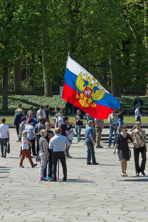 treptow: BERLIN - MAY 09, 2016: Victory Day in Treptower Park. Guests and visitors at the war memorial with a large Russian flag.