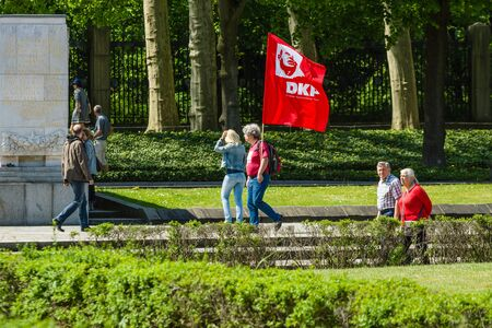 soviet flag: BERLIN - MAY 08, 2016: Victory in Europe Day. Soviet War Memorial and military cemetery in Berlins Treptower Park. A visitor with the flag of the German Communist Party.
