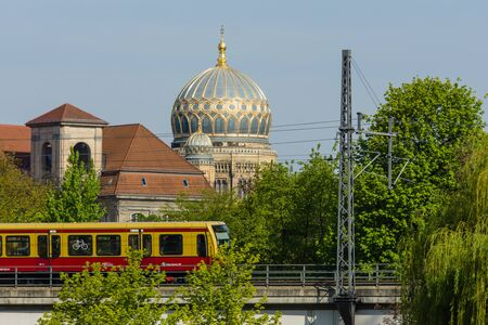 synagoge: BERLIN - MAY 01, 2016: Urban rail S-Bahn (foreground) on the background of the dome Neue Synagoge (New Synagogue). Editorial