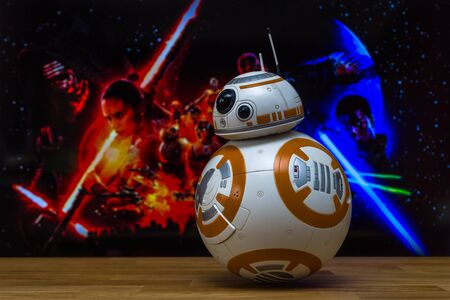 saga: BERLIN, GERMANY - JUNE 10, 2016: BB-8 Android Models on the background of the official poster of the new movie of the saga Star Wars: The Force Awakens.