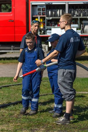 east berlin: BERLIN - JUNE 11, 2016: Berlin firefighter shows a group of children skills of working with fog nozzle. German-Russian festival devoted to the Independence Day of Russia. District Karlshorst, East Berlin. Editorial