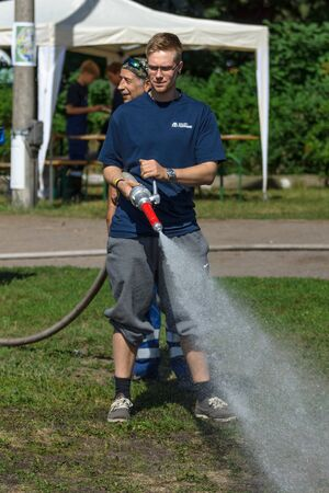 east berlin: BERLIN - JUNE 11, 2016: The Berlin firefighter shows skills of working with fog nozzle. German-Russian festival devoted to the Independence Day of Russia. District Karlshorst, East Berlin.
