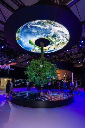 astronautics: BERLIN, GERMANY - JUNE 01, 2016: Pavilion space. Model Earth and a growing green tree. Exhibition ILA Berlin Air Show 2016