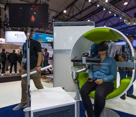 flight helmet: BERLIN, GERMANY - JUNE 01, 2016: The stand of Airbus Group. Flight simulator based on virtual reality glasses Oculus Rift. Exhibition ILA Berlin Air Show 2016.