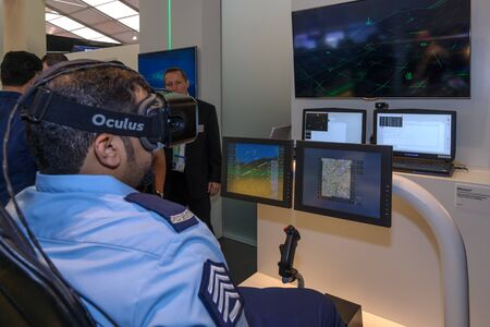 situational: BERLIN, GERMANY - JUNE 01, 2016: The stand of the company Airbus Defense & Space. A military in glasses Oculus Rift at the console flight simulator Sferion. Exhibition ILA Berlin Air Show 2016. Editorial