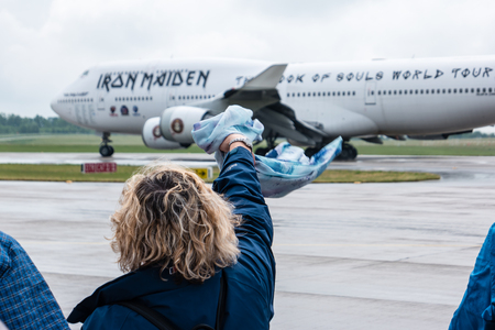 747 400: BERLIN, GERMANY - JUNE 01, 2016: A woman says goodbye to Iron Maidens Boeing 747 Ed Force One. Focus on the foreground. The world tour The Book of Souls. Exhibition ILA Berlin Air Show 2016