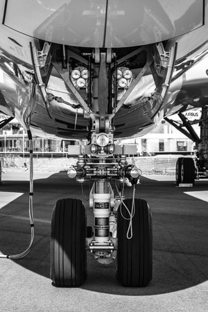 newest: BERLIN, GERMANY - JUNE 02, 2016: Front landing gear of the newest airplane Airbus A350-900 XWB. Black and white. Exhibition ILA Berlin Air Show 2016