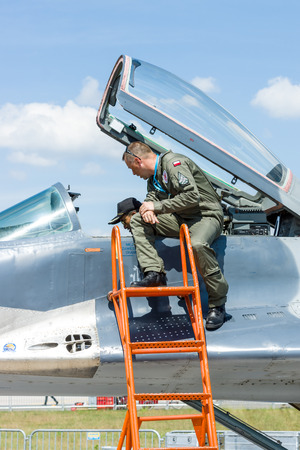 fighter pilot: BERLIN, GERMANY - JUNE 03, 2016: The pilot and the visitor near the cockpit of the multirole fighter Mikojan-Gurewitsch MiG-29. Polish Air Force. Exhibition ILA Berlin Air Show 2016