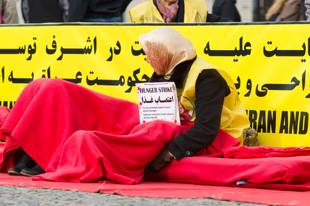 iraq: BERLIN, GERMANY - OCTOBER 25, 2013: The action (hunger strike) Iranian dissidents in front of the Brandenburg Gate in Berlin dedicated to the massacre in Camp Ashraf.