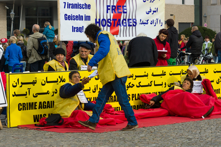 BERLIN, GERMANY - OCTOBER 25, 2013: The action (hunger strike) Iranian dissidents in front of the Brandenburg Gate in Berlin dedicated to the massacre in Camp Ashraf.