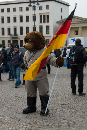 BERLIN, GERMANY - NOVEMBER 01, 2013: The Bear - a symbol of Berlin, in the uniform of soldier of the GDR on the background of the Brandenburg Gate. Editorial