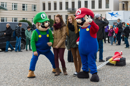 mario: BERLIN, GERMANY - NOVEMBER 01, 2013: Tourists take photos with the characters of the famous computer game Mario Brothers at Pariser Platz in front of the Brandenburg Gate. Editorial