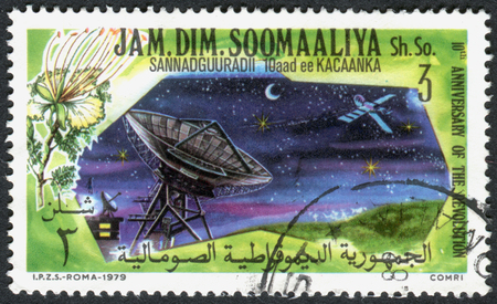 SOMALIA - CIRCA 1979: A stamp printed in Somalia, dedicated to the 10th anniversary of the revolution, shows a satellite communication station, circa 1979 Editorial