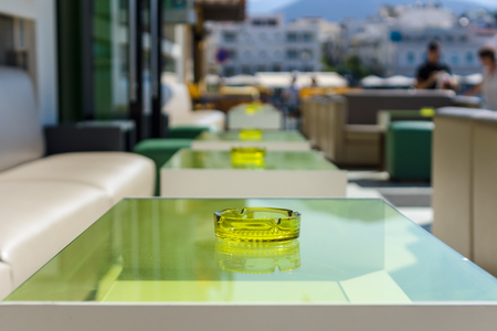 porch scene: An empty table with an ashtray in a street restaurant. Focus on the foreground.
